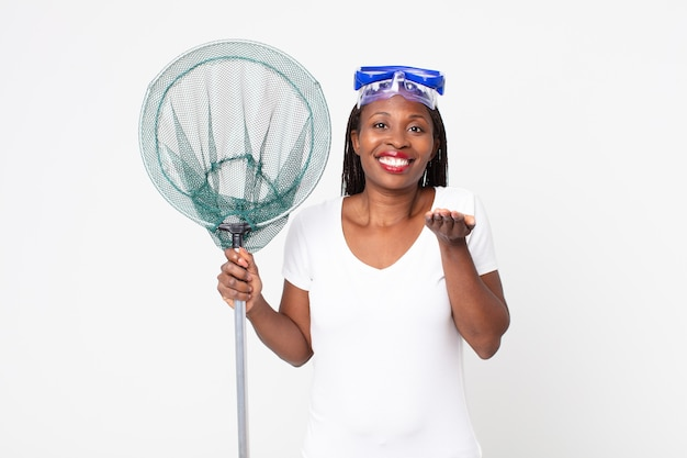 Sonriendo alegremente con amables y ofreciendo y mostrando un concepto con gafas y red de pesca