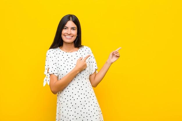 Sonriendo alegremente y apuntando hacia un lado y hacia arriba con ambas manos mostrando el objeto en el espacio de la copia