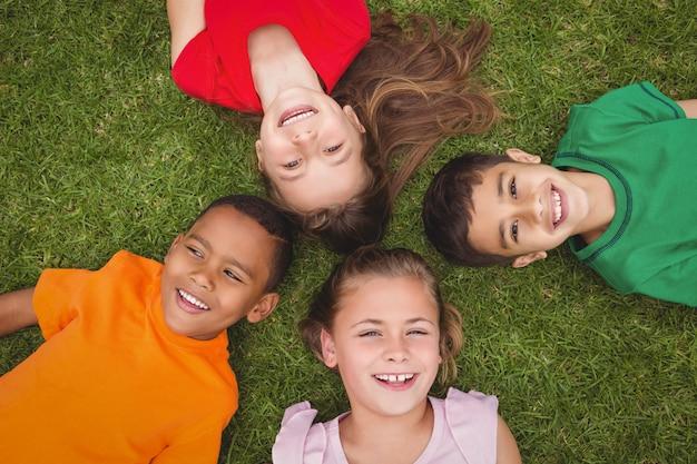 Sonriendo alumnos tumbados en el suelo
