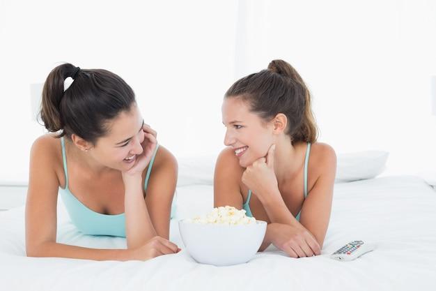 Sonriendo amigas con tazón de palomitas acostado en la cama
