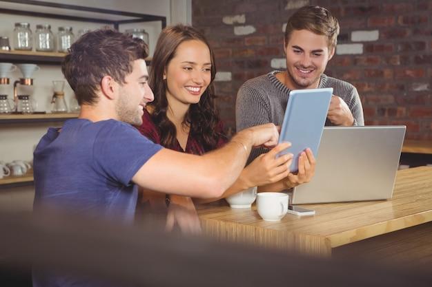 Sonriendo amigos apuntando y mirando tablet pc