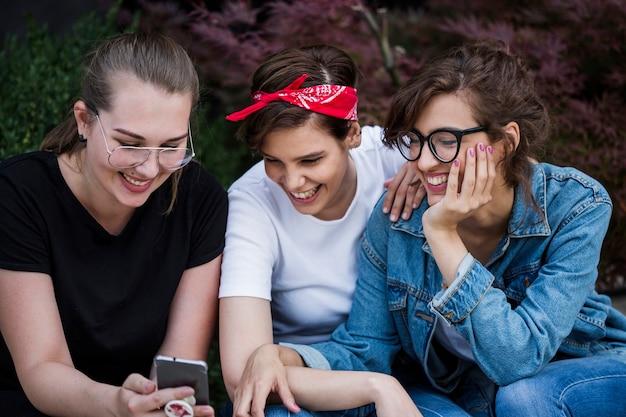 Sonriendo amigos mirando la pantalla del teléfono inteligente