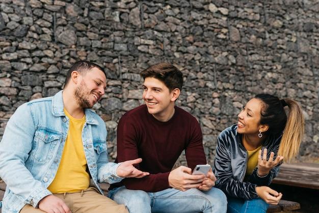 Sonriendo amigos multiétnicos hablando y mirando el teléfono