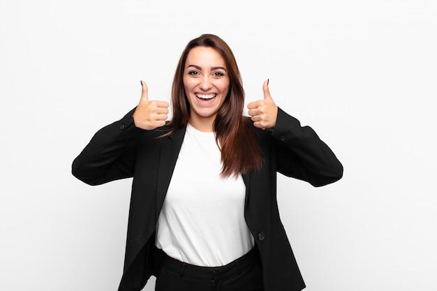 Sonriendo ampliamente, feliz, positivo, seguro y exitoso, con ambos pulgares arriba