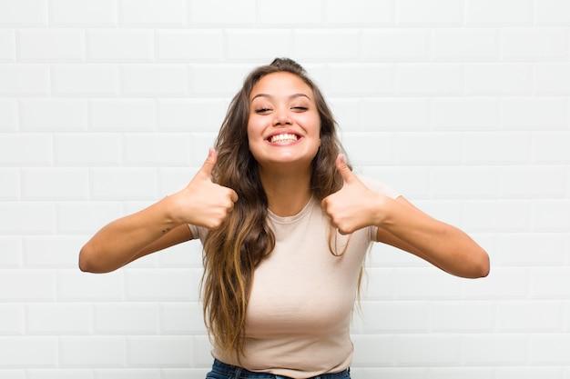 Sonriendo ampliamente luciendo feliz, positivo, seguro y exitoso, con ambos pulgares hacia arriba