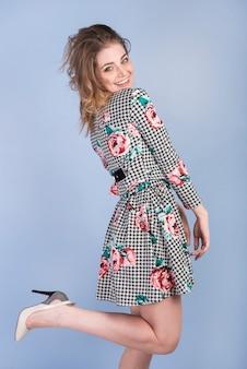 Sonriendo apasionada mujer en vestido y tacones altos.