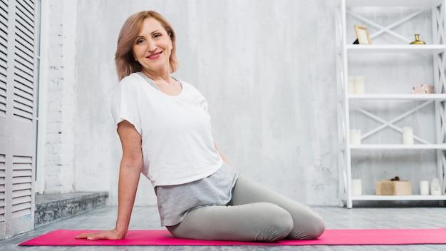 Sonriendo apta a la mujer mayor que se sienta en la estera de la yoga que mira la cámara