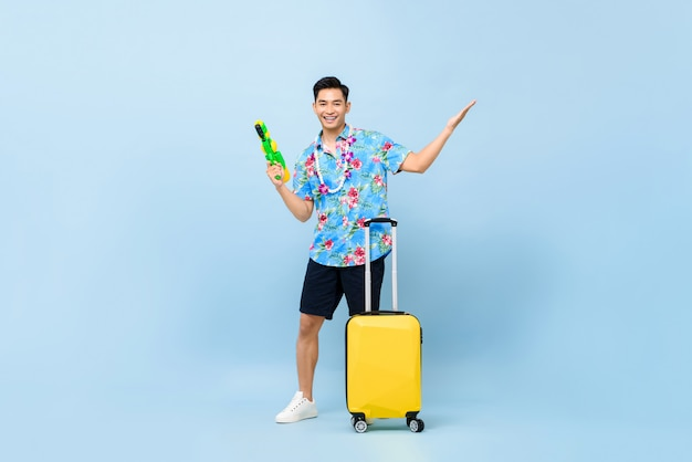 Sonriendo apuesto hombre turista asiático que viaja con pistola de agua y equipaje durante songkran