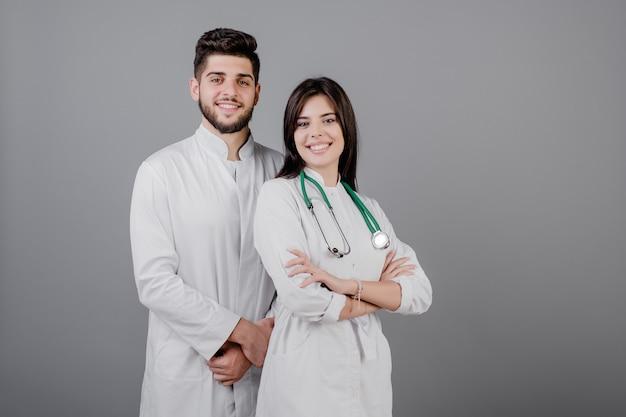 Sonriendo apuestos médicos en batas sonriendo aislado sobre gris