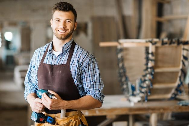 Sonriendo artesano con taladro eléctrico