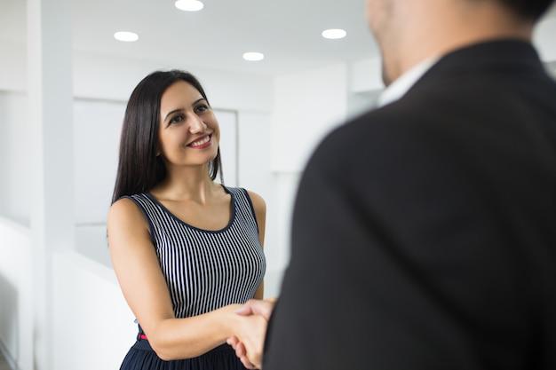 Sonriendo atractiva empresaria haciendo apretón de manos con pareja