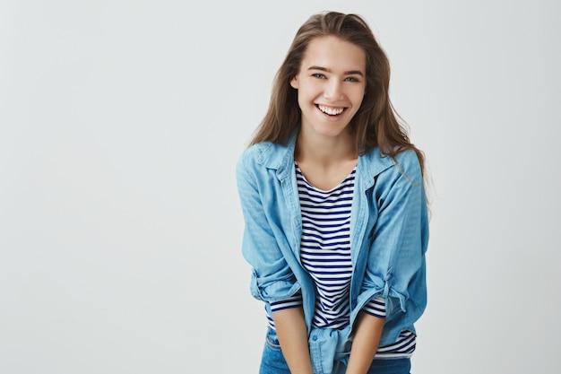 Sonriendo atractiva joven feliz riendo despreocupada divirtiéndose sonriendo alegremente inclinándose hacia adelante tonto lindo, posando tonto. tierna mujer europea riéndose coqueta mirando, de pie