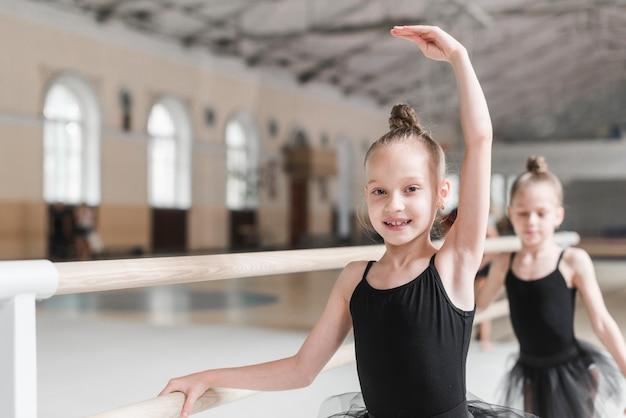 Sonriendo bailarín de ballet practicando con barre en clase de baile