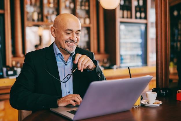 Sonriendo barbudo adulto mayor en traje con anteojos en la mano y usando la computadora portátil mientras está sentado en la cafetería.