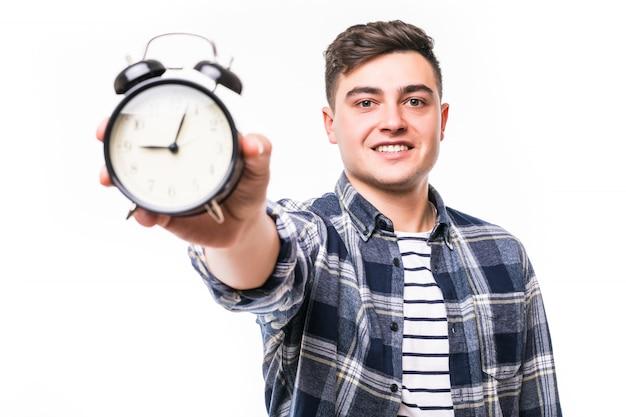 Sonriendo bastante joven mostrando tiempo en reloj despertador negro