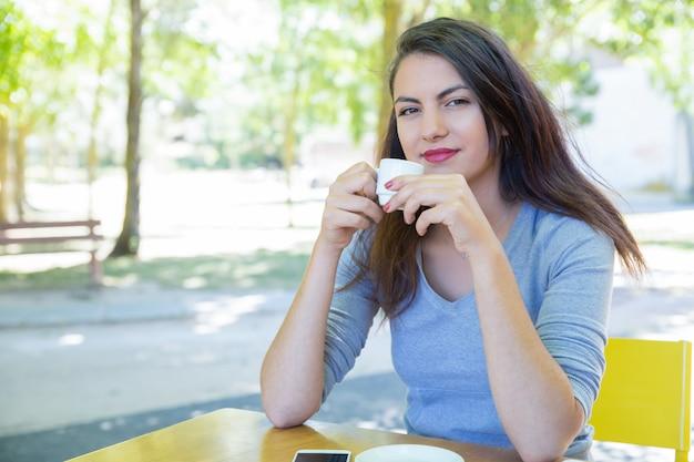 Sonriendo bastante jovencita tomando café en la mesa de café en el parque