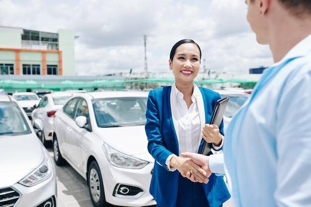 Sonriendo bastante vendedora de concesionario de coches vietnamita en traje de estrechar la mano del cliente