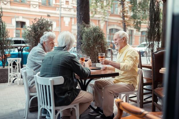 Sonriendo y bebiendo. hombres jubilados de pelo gris sonriendo y bebiendo alcohol sentados fuera de pub