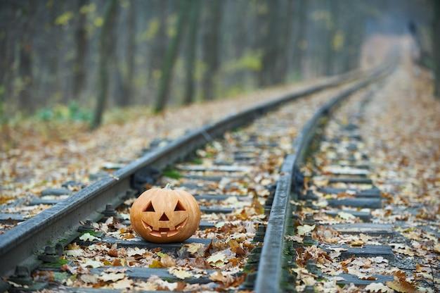 Sonriendo calabaza de halloween en los rieles en el bosque