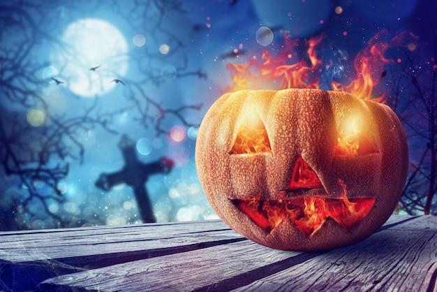 Sonriendo calabaza tallada de halloween con fuego en un cementerio
