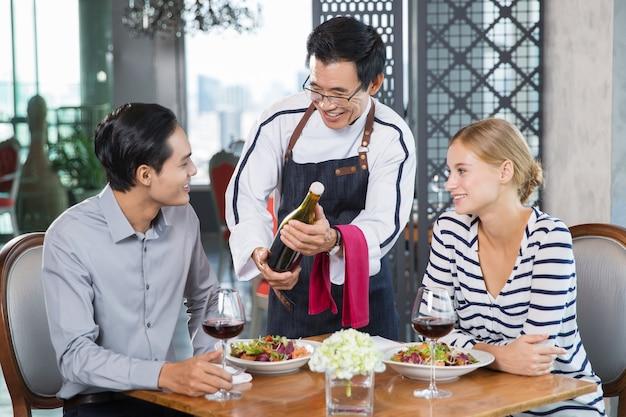 Sonriendo camarero asiático que ofrece el vino a pareja joven Foto gratis