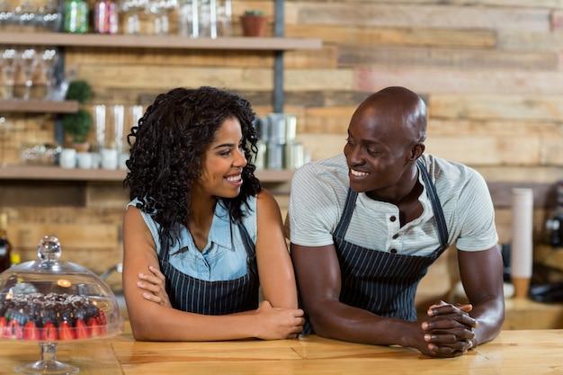 Sonriendo camarero y camarera interactuando entre sí en el mostrador