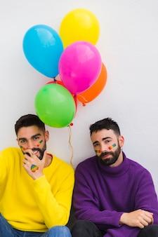 Sonriendo y cansados gays sentados con globos.