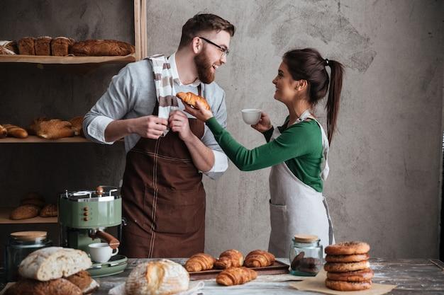 Sonriendo cariñosa pareja panaderos bebiendo café.