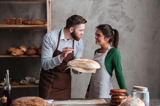Sonriendo cariñosa pareja panaderos de pie en la panadería con pan