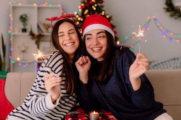 Sonriendo a chicas guapas con gafas de reno y gorro de papá noel sosteniendo y mirando bengalas sentados en sillones y disfrutando de la navidad en casa