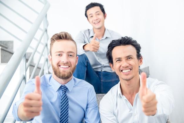 Sonriendo colegas mostrando pulgares en las escaleras