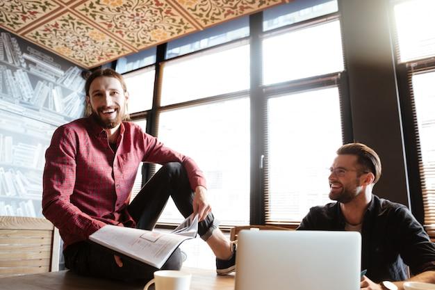 Sonriendo colegas sentados en la oficina trabajando con documentos.