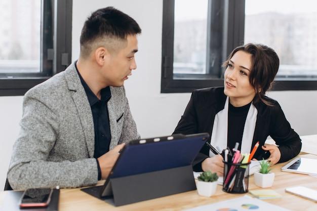Sonriendo colegas de trabajo sentados juntos en una mesa en una oficina moderna hablando y usando una tableta