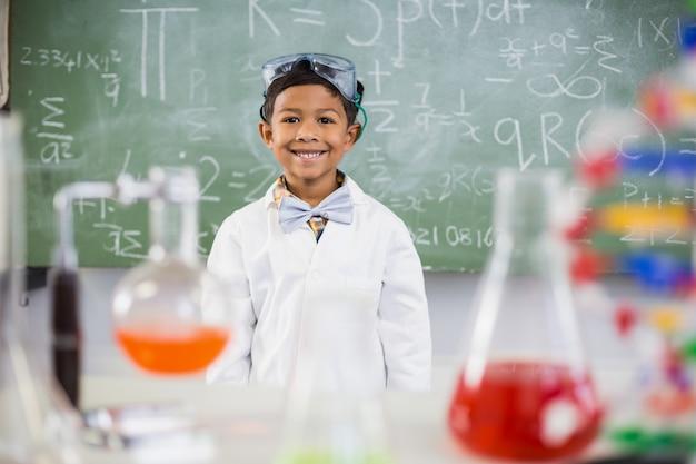 Sonriendo colegial de pie en el aula con matraz químico en primer plano