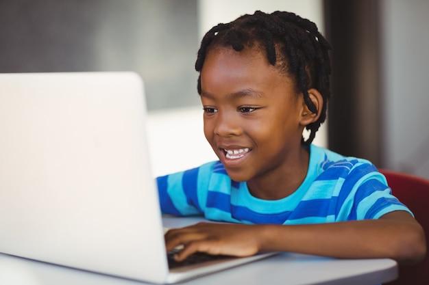 Sonriendo colegial usando laptop en el aula