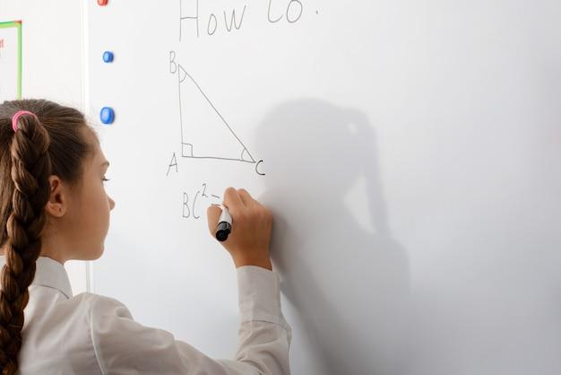 Sonriendo colegiala haciendo tarea de geometría matemática en marcador blanco