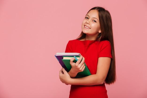 Sonriendo colegiala sosteniendo libros y mirando