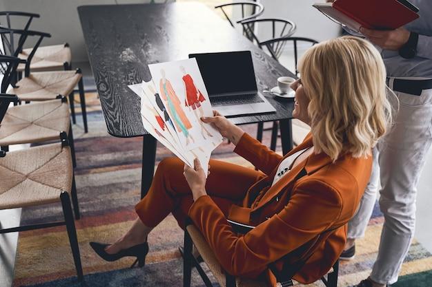 Sonriendo complacida rubia joven diseñadora de moda caucásica trabajando en un estudio con su colega masculino