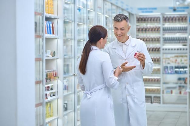 Sonriendo complacido atractivo farmacéutico masculino caucásico y su compañera de trabajo de pie en el almacén de la farmacia