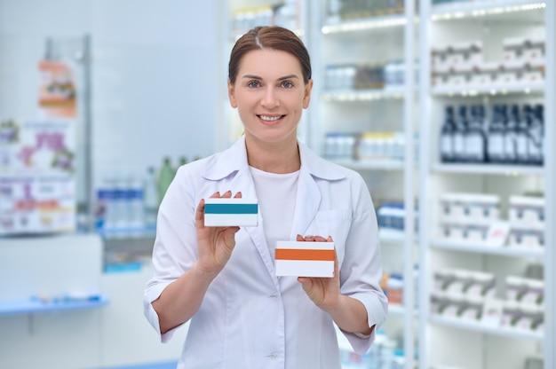 Sonriendo complacido hermosa farmacéutica sosteniendo dos cajas de cartón con medicamentos frente a ella