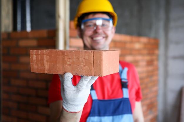 Sonriendo constructor masculino mostrando material de ladrillo de buena calidad en la cámara