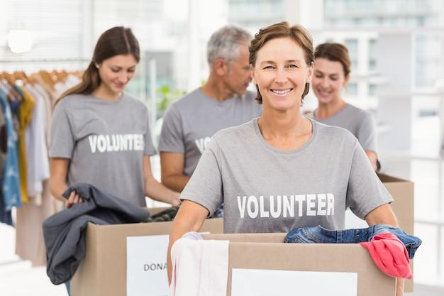 Sonriendo cuadro de donación voluntario femenino que lleva