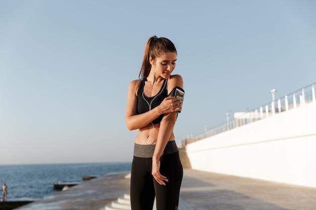 Sonriendo deportes joven mujer escuchando música con teléfono móvil.