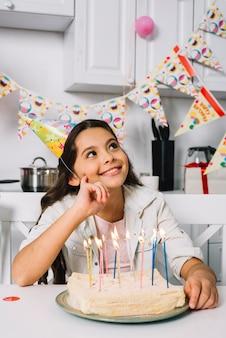 Sonriendo día soñando niña sentada frente a pastel de cumpleaños con velas iluminadas
