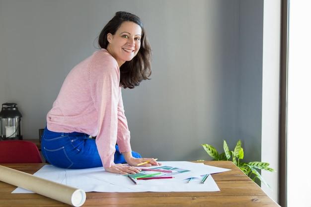 Sonriendo diseñador de interiores positivo trabajando en proyecto de renovación