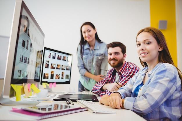 Sonriendo diseñadores gráficos en el escritorio