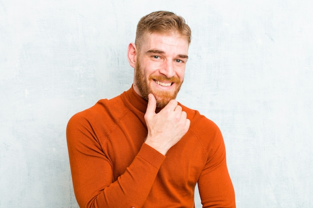 Sonriendo, disfrutando la vida, sintiéndose feliz, amigable, satisfecho y despreocupado con la mano en la barbilla