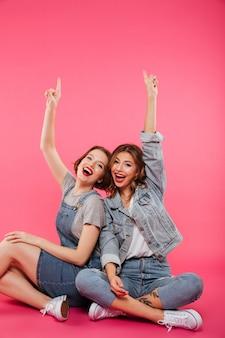 Sonriendo dos amigas sentadas en el piso