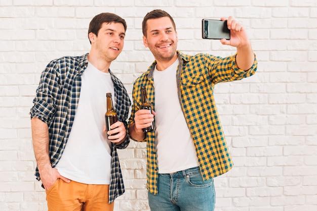 Sonriendo dos amigos varones sosteniendo una botella de cerveza tomando selfie en el teléfono móvil