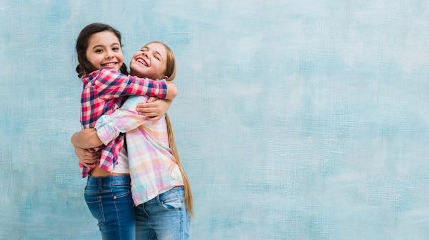 Sonriendo dos chicas abrazando de pie contra la pared pintada de azul